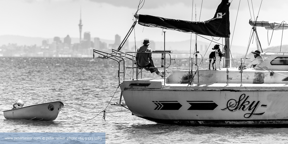 Two occupants and a dog on the yacht, Sky, anchored at Motuihe Island. Downtown Auckland skyline in the background. Waitemata Harbour, Auckland.