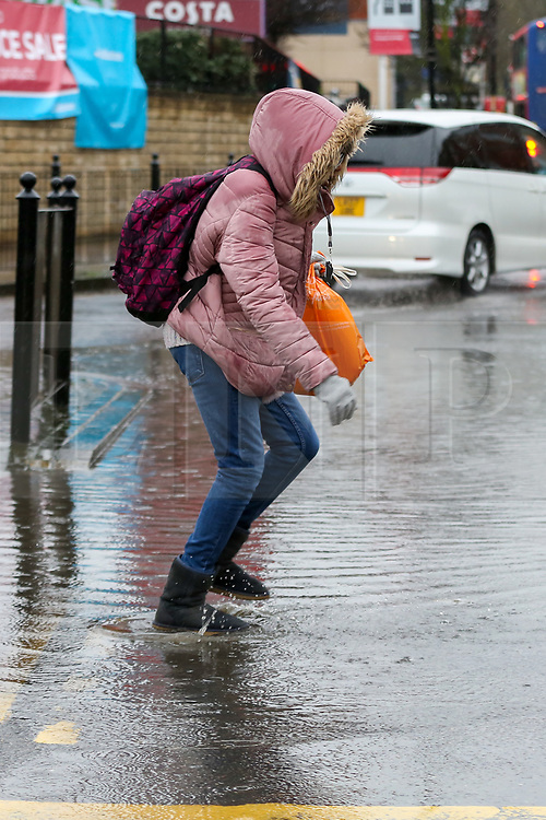 © Licensed to London News Pictures. 15/01/2020. London, UK. A member of public walks through a flood on Green Lanes in north London following heavy overnight rainfall. Photo credit: Dinendra Haria/LNP
