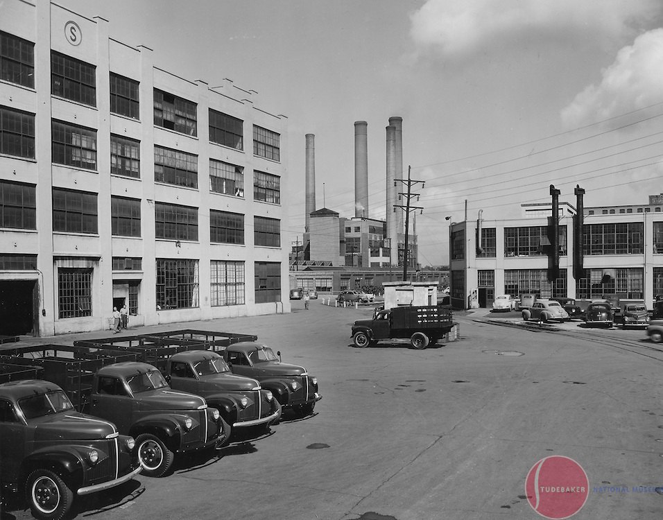 New Studebaker M-Series trucks sit outside building #78 at the company's South Bend plant.  The Studebaker Engineering Building is visible in the background, as is the power plant (smokestacks.)
