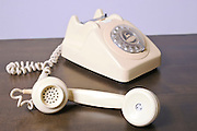 Cutout of a retro ivory coloured telephone on white background