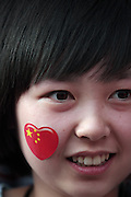 A young Chinese woman wears a nationalistic sticker on her cheek at  the Olympic Torch relay in the southern city of Wuhan, China.