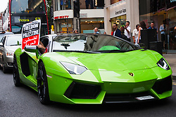 "London, July 5th 2014. A passenger in a foreign-registered Lamborghini supports a protest near the Israeli embassy in London, against the ongoing occupation of Palestine and the west's support of ""Israel's collective punishment of Palestinians""."