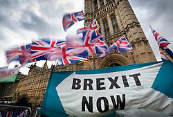 © Licensed to London News Pictures. 30/09/2019. London, UK. Union flags flutter above a banner outside Parliament saying 'BREXIT NOW'. Earlier a meeting of opposition leaders was held to discuss a plan to force the Prime Minister to go to Brussels to seek another Brexit delay as early as this weekend. Photo credit: Peter Macdiarmid/LNP