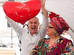 © Licensed to London News Pictures. 14/06/2012. LONDON, UK. Artist Damien Hirst (L) holds aloft a heart, created by spinning, as he poses with Kids Company founder Camilla Batmanghelidjh (R) in Covent Garden, London, today (14/06/12). In celebration of Damien Hirst's current exhibition at the Tate Modern, the artist held a pubic art event giving British School children the chance to create their own versions of his iconic spin paintings. Photo credit: Matt Cetti-Roberts/LNP