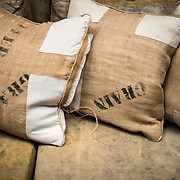 Rustic burlap sofa pillows  with the words Grain and Feed stamped on them.