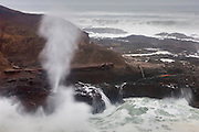 Pacific Ocean waves spray high into the sky through a blowhole name Spouting Horn at Cape Perpetua, Oregon. Blowholes are essentially skylights in ocean caves. At high tide, water fills the cave and the pressure from incoming waves forces the water through the small opening and high into the sky.