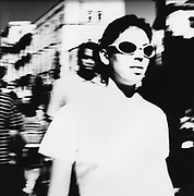 A blurred picture of a girl in sunglasses walking down the street, 1980's.