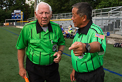 Soccer linesman Aubrey Cashman, right, talks with colleague linesman Henry Woo during a soccer match between Lexington Catholic and Henry Clay, Tuesday, Aug. 13, 2013 at Lexington Catholic Soccer/Football Stadium in Lexington. Photo by Jonathan Palmer