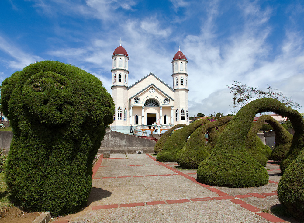 Zarcero, Central Highlands: Topiaries shaped like arches, monkeys, elephants, cats, a motorcycle, a bull ring, and so on have brought international fame to this small mountain town about an hour's drive northeast of San Jose.  These topiaries, shaped from cypress bushes, fill the Parque Central (Parque Francisco Alvarado) in front of the town's main church, another thing of unique beauty in itself.  The topiaries are the work of Evangelisto Blanco, the parque's gardener, a project that began more than 40 years ago. Today, these clever topiaries are known the world over and often compared to other unique art forms such as the works of Gaudi in Spain and Rodia in Los Angeles, California.  They form a frame and entrance to the Iglesia de San Rafael, known as the pink and blue church.