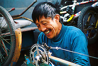 China, Beijing, 2007. Repairmen are crucial to China's disappearing bicycle culture. An inner tube hung on a tree or a pump standing up on the street helps people find these important and frequently cheerful laborers. .