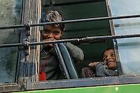 A boy in the open window of a school bus, Delhi, India.