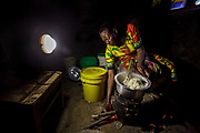 At her home near Arusha, Tanzania Solar Sister entrepreneur Julieth Mollel  prepares a dinner of ugali, vegetables and beans cooking on her clean cookstove. Ugali is a staple eaten in many countries in Africa and is cornmeal porridge. Working in her compact outdoor kitchen at night is easier now both with the clean cookstove that puts out very little smoke and uses only a fraction of the firewood of a traditional three-stone cookstove but also with her Solar Sister solar lantern to light up the area brightly while she works.                                                 Julieth Mollel has not had an easy life. Julieth and her husband are from the Masai tribe and live in northern Tanzania about an hour outside of Arusha near the southern slopes of Mount Meru. Julieth has toiled all of her life farming, selling crops and keeping the house for her husband and children. Now at sixty-one (61) she works hard to keep the family going and to pay the fees to send her grandchildren to school.<br />  <br /> Until she started working for Solar Sister in Tanzania life was becoming almost unbearable for Julieth. Cooking over her traditional cook stove made of three stones and an open fire pit put out a lot of smoke that she breathed in when she cooked breakfast, lunch and dinner for her family. <br /> <br /> The stove required a lot of firewood so daily she had to go out and bring home a huge bundle of wood. Over time she began to have severe pains in her chest and had difficulty picking up and carrying the firewood back home. Juileth has had to walk farther and farther to get firewood as the years have passed due to the cutting down of trees in the area to expand farms and build settlements as well as the collection of firewood for cooking and making charcoal.<br /> <br />  During this time Julieth was struggling to still pay the fees for her grandchildren to attend school but it was getting harder and harder and she was just about at the end of her rope and falling into despa