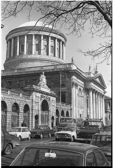 """The Four Courts..1971..16.04.1971..04.16.1971..16th April 1971..The Four Courts,for centuries,has been the centre of Ireland's Judicial system..Work based on the designs of Thomas Cooley, architect of the Royal Exchange (now City Hall), began in 1776. Cooley's building concentrated in the area of the west courtyard and was intended to house only the Public Records Office and King's Inns. When Cooley died in 1784, James Gandon, architect of the Custom House, was appointed to add the courts to the plan. Into his completed design he incorporated Cooley's building, adding two quadrangles and a central block. The quadrangles were given to the record and legal offices, the centre to the four courts of Chancery, Exchequer, Kings Bench and Common Pleas. At the hub is the Round Hall, 64ft in diameter, with inner and outer domes and a surround of Corinthian columns. It was once described as """"both the physical and spiritual centre of the building""""(www.courts.ie/courts.ie/library3.).Throughout the years the courts have been damaged ,destroyed and rebuilt as a result of rebellion and the Irish civil war..A photograph of the Four Courts showing the dome and the collanaded front of the building."""