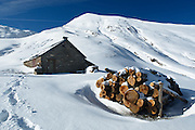 Firewood piled outside a mountain shelter in snowy mountain landscape near Col de Pause, Ariege, Pyrenees, France.