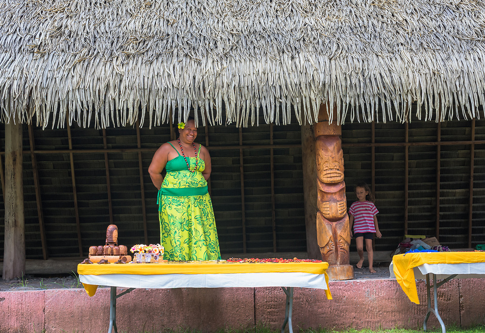 Nuku Hiva, French Polynesia -- March 23, 2018. A Nuku Hiva merchant stands behind a display of goods for sale at an outdoor market. Editorial Use Only.