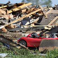 A child's toy car sits just feet away from piles of debris as the President's Gate Apartments are being torn down Thursday.