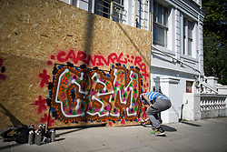 © Licensed to London News Pictures. 23/08/2019. London, UK. A graffiti artist paints on boarding protecting residential property as preparations in Notting Hill, West London begin of the 2018 Notting Hill Carnival which starts this weekend. Warm weather is expected over the bank holiday weekend with carnival attracting over 1 million people to the capital. Photo credit: Ben Cawthra/LNP