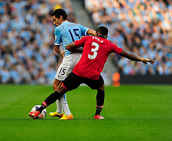 Manchester United's Patrice Evra tackles Manchester City's Jesus Navas - Photo mandatory by-line: Dougie Allward/JMP - Tel: Mobile: 07966 386802 22/09/2013 - SPORT - FOOTBALL - City of Manchester Stadium - Manchester - Manchester City V Manchester United - Barclays Premier League