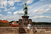 "A woman standing in-front of the statue of  ""John of Nepomuk"" which is an outdoor sculpture, installed in 1683 on the north side of the Charles Bridge in Prague, Czech Republic. The Czech government lowered the security measures and as of Monday 25 May 2020, wearing of protective masks will be mandatory only in the interiors of buildings other than the place of residence and in public transport."