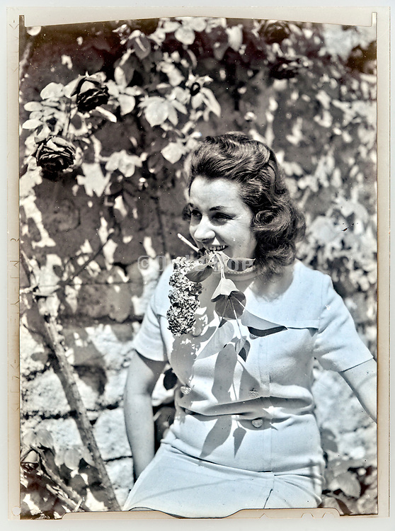 woman holding flower in mouth portrait  around 1960s period