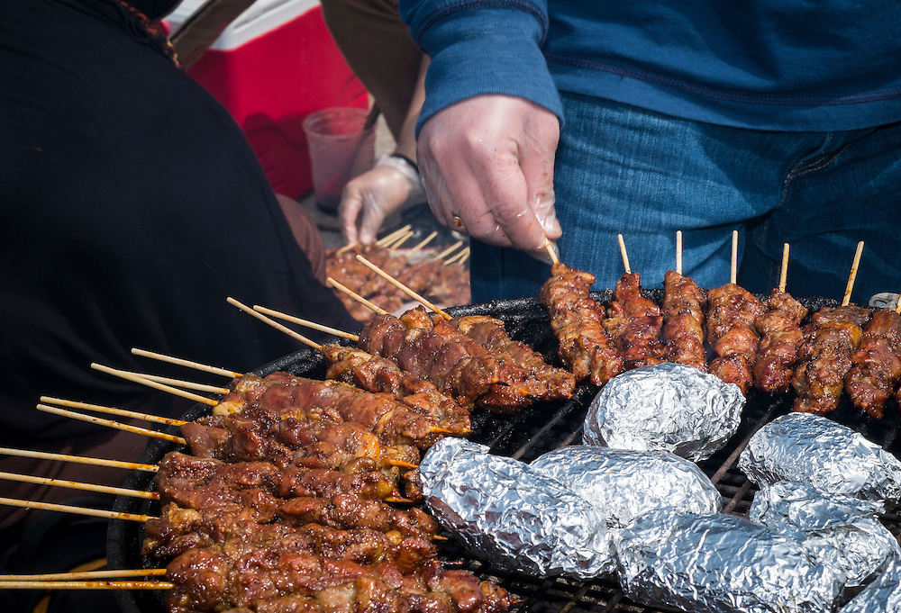 Airlangga Dermawan works the grill for the Indonesian Students Association table at the International Street Fair on Saturday, April 18, 2015.  Photo by Ohio University  /  Rob Hardin