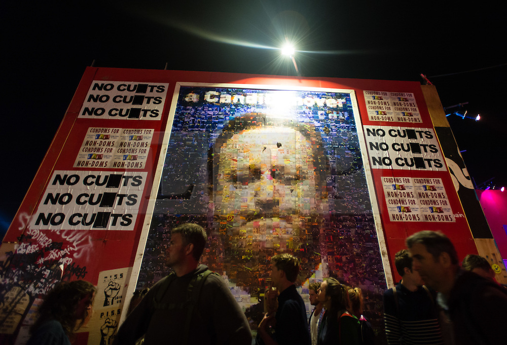 © Licensed to London News Pictures. 27/06/2015. Pilton, UK.  Night-time festival atmosphere at Glastonbury Festival 2015 in the Shangri-La area of the festival on Saturday Day 4 of the festival a big wall with a picture of David Cameron alongside the slogan No Cu*ts (the letter after U is marked out).  Shangri-La is a destroyed dystopian pleasure city.  This years headline acts include Kanye West, The Who and Florence and the Machine, the latter being upgraded in the bill to replace original headline act Foo Fighters. Photo credit: Richard Isaac/LNP