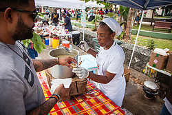 "Alexandrina Anthony serves a ""Everything Local"" stew full of local ingredients including pumpkin, chicken, papaya, cristofin, and green bananas.  Coal Pot Cook-Off  at Emancipation Garden raising funds for St. Thomas Historical Trust.  St. Thomas, VI.  19 May 2015.    © Aisha-Zakiya Boyd"