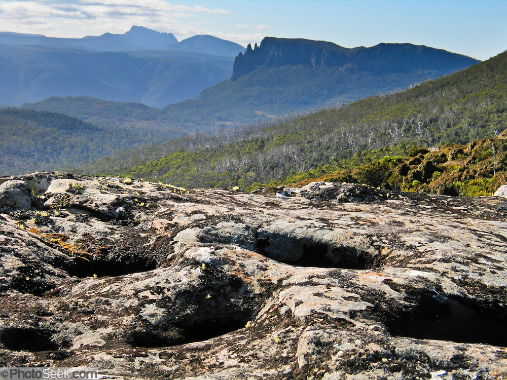 From Pelion Gap on the Overland Track, see Cradle Mountain and natural rock potholes in Cradle Mountain-Lake St Clair National Park, Tasmania, Australia. The most extensive dolerite formations in the world dominate the landscape of Tasmania, where magma intruded into a thin veneer of Permian and Triassic rocks over perhaps a million years during the Jurassic breakup of supercontinent Gondwana in the Southern Hemisphere, forming vast dolerite/diabase sills and dike swarms. (North American geologists use the term diabase instead of dolerite to refer to the fresh, unaltered rock.) The Tasmanian Wilderness was honored as a UNESCO World Heritage Site in 1982, expanded in 1989. The famous Overland Track features mountains, temperate rainforest, wild rivers, alpine plains, abundant birds, and other wildlife.