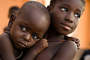 A young girl holds a younger sibling in the village of Chaalam, Ghana on Tuesday June 5, 2007. Taking care of young children is often the job of girls in Ghana, as women often need to work in the fields and can't stay home.