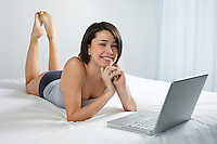Young woman using laptop lying on bed portrait
