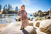 Stylish young girl showing off rural, hippie kids fashion clothing at a Lake Tahoe Beach in Incline Village, Nevada.
