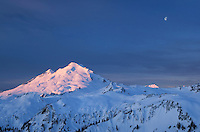 The moon hangs over Mount Baker, 10,781 ft (3,286 m) while the snows and glaciers glow in the light of a winter dawn. North Cascades Washington