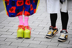 © Licensed to London News Pictures. 04/06/2018. London, UK.  The shoes of (L) Grayson Perry RA and (R) Rose Wylie RA at a photocall to celebrate the 250th anniversary of the Royal Academy's Summer Exhibition where over 200 flags, designed by celebrated Royal Academicians, decorate the streets of the West End.  Photo credit: Stephen Chung/LNP