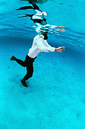 A fully clothed man in to his neck in water is trying to make head way walking through deep water. Tonga
