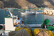 A fisherman working on his nets in the harbour at Kamares, Sifnos, The Cyclades, Greek Islands, Greece, Europe
