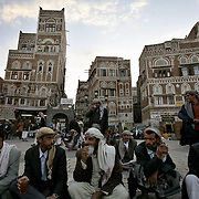 Men drink tea and chew qat by the Bab al Yemen, the gate of the old city of San'aa, at dusk.