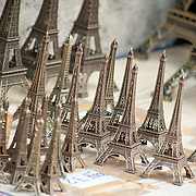 Miniature Eiffel Tower replicas for sale at a souvenir stall.