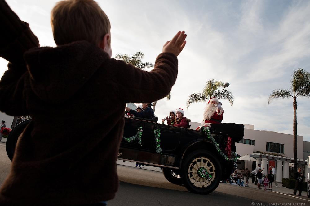 Ajay Sembach, 5, waves to Santa as the 2009 La Jolla Christmas Parade heads down Prospect Street.