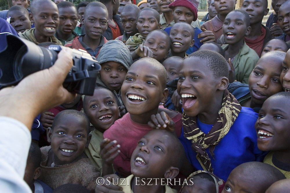 Children looking at photo of themselves in tourist's camera <br /> At a cultural village near Kinigi at border of Virunga Volcanoes National Park, Rwanda