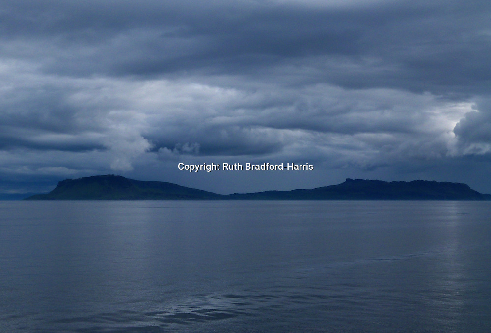 Spectacular individual storm cells dropping down from a dramatic mass of cumulonimbus clouds to the peaks of the Beinn Bhuidhe plateau and An Sgurr ridge on the Isle of Eigg. Photograph taken from a boat on the Sound of Rum.<br />