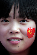 A young woman wears a Chinese flag sticker on her cheek at the Olympic Torch relay in the southern city of Wuhan