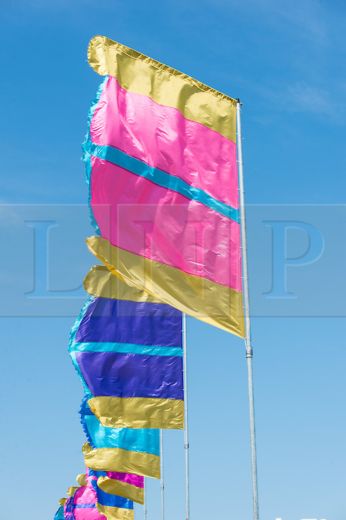© Licensed to London News Pictures. 11/06/2015. Newport, UK.  Brightly coloured festival flags fly under a deep blue sky at the Isle of Wight Festival 2015, as festival goers arrive on day 1 of the festival.  This years festival include headline artists the Prodigy, Blur and Fleetwood Mac.  Photo credit : Richard Isaac/LNP