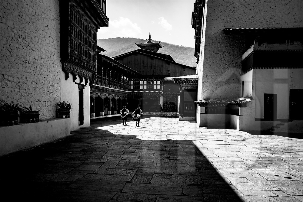 Buddhist monks walk through a yard of Rinpung Dzong monastery, Paro, Nepal, Asia