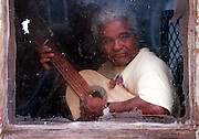 Domingo Degros, 67, plays a 'Quinto al Aire' on his Puerto Rican cuatro while keeping an eye peeled for customers at his Broad St. soft drink sidewalk business in Hartford's Frog Hollow neighborhood. Degros says that the cuatro is a unique type of guitar that is  constructed and widely used in Puerto Rico.