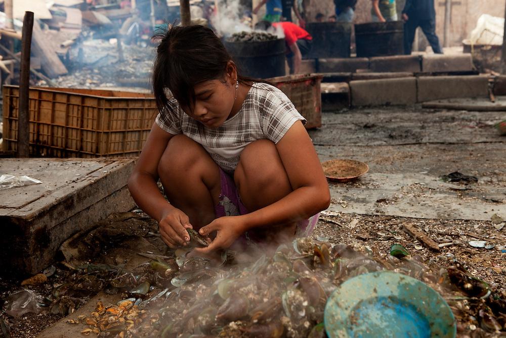 Women break shellfish for a living in Slum area in North Jakarta, Jakarta, Indonesia.