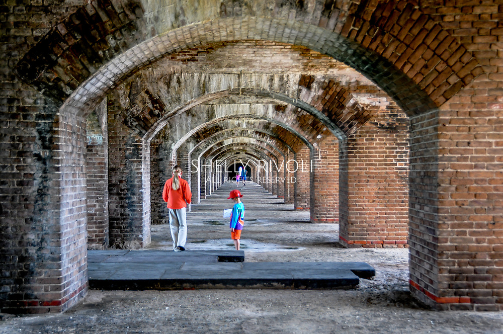 Kids explore the interior of Fort Jefferson walking beneath brick arches on a family day trip to Dry Tortugas National Park from Key West, Florida. Model released photo.