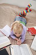 Teenage girl (16-17) doing homework lying on bed