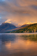 Curtains of rain showers from a passing autumn storm glow in the evening light above Lake McDonald, Glacier National Park Montana USA