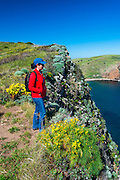 Hiker enjoying the view above Scorpion Cove, Santa Cruz Island, Channel Islands National Park, California USA
