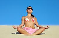 beautiful smiling bikini dressed young brazilian  woman meditating on lotus posture on the sand dune of  jericoacoara ceara state near fortaleza